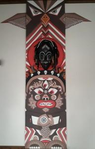 Totemická malba na zeď. Ve spodní části hněvivé božstvo, z vrcholu shlíží mýtický pták (Garuda), uprostřed tradiční africká maska symbolizující člověka. 2018